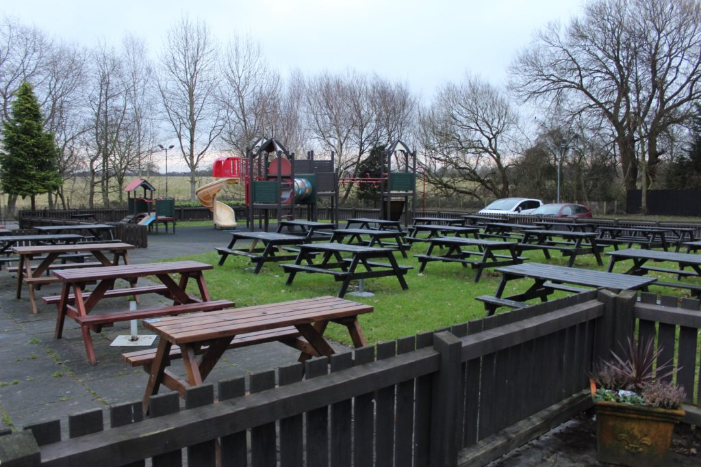 large beer garden outside drinking area and children's outside play area at The George and Dragon pub at at Glazebury.
