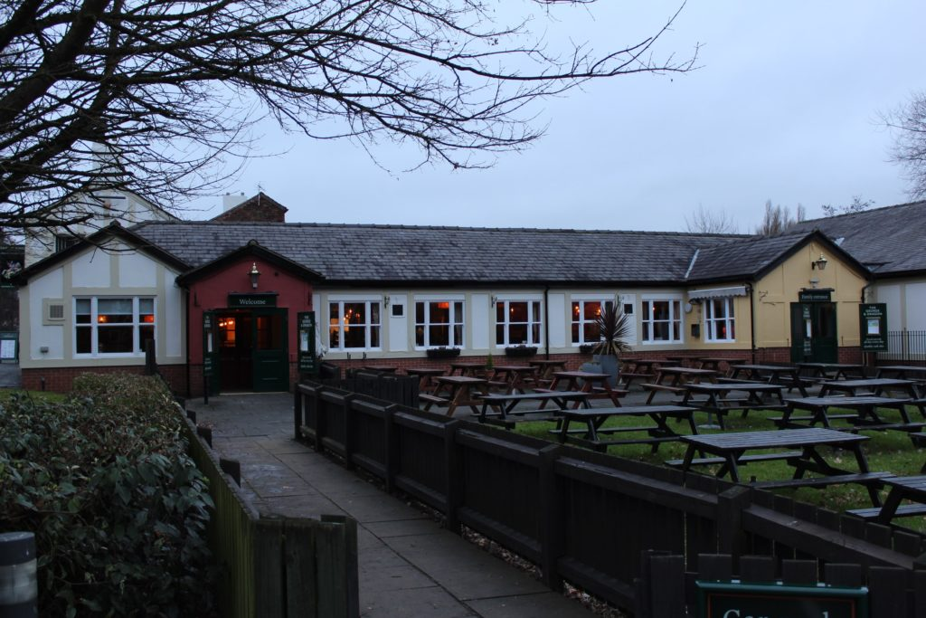 Exterior and large outside drinking area at The George and Dragon pub at at Glazebury.